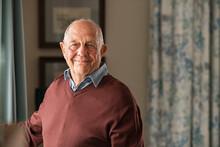 Happy Senior Man Looking At Camera At Home