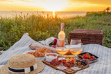 Picnic with strawberries, croissants and appetizers on the board and rose wine.