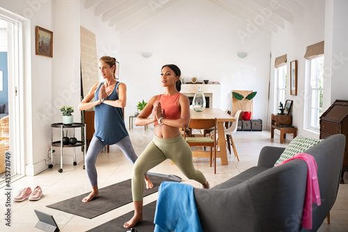 Foto Mid adult multiethnic women practicing yoga together at home