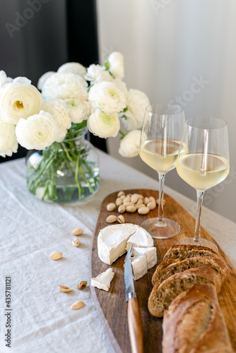 Fotografering Two glasses of white wine and a wooden board with appetizers on the table