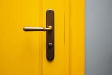 Yellow Door With A Bronze Door Handle Close-up.