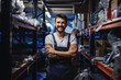 Leinwandbild Motiv Young smiling happy tattooed bearded worker in overalls standing in storage of import and export firm with arms crossed.