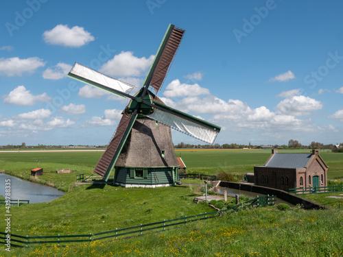 Obraz na płótnie Dutch windmill in polder landscape with beautiful clouds