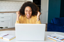 Excited Happy African-American Freelancer Woman Yelling Yes, Looking At The Laptop Screen, Celebrating Victory, Goal Achievement, Black Female With Afro Hairstyle Raised Fists Up, Received Opportunity