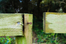 Wooden Fence Post With Rusty Nail And Gap In The  Rail