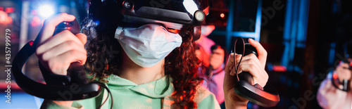 Foto cropped view of african american girl in medical mask gaming in vr play zone, ba