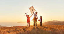 Happy Family  Mother And Kids  Launch  Kite On Nature At Sunset