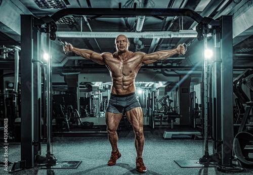 Bodybuilder athlete trains in the gym Fotobehang