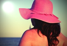 Young Woman From Behind With Big Straw Hat And Sun In Backlight With Antiqued Effect