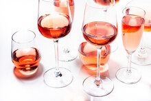 Rose Wine Glasses Set On Wine Tasting. Different Varieties, Colors And Shades Of Pink Wines On White Background. Top View