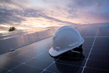 Helmet Of Engineer Working On Checking Equipment In Solar Power Plant, Photovoltaic Modules For Renewable Energy