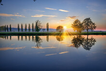 Stunning View Of A Brightly Shining Sun And Trees Reflected In A Mirror-like Lake During Sunset