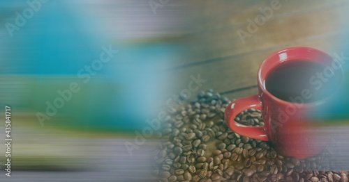 Composition of red cup of coffee with coffee beans forming heart over wooden surface with copy space