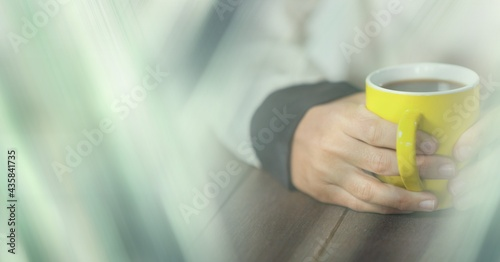 Composition of woman holding yellow cup of coffee over wooden surface with copy space