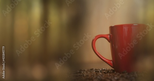 Composition of red cup of coffee with coffee beans over wooden surface with copy space