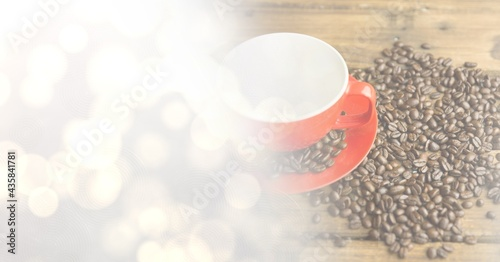 Composition of red cup and saucer with coffee beans over wooden surface with copy space