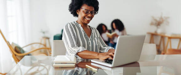 Happy woman working from home on laptop
