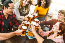 Happy Multiracial Friends Toasting Beer Glasses At Brewery Pub - Group Of Young People Having Fun Hanging Out Drinking At Rooftop Bar Restaurant - Focus On Glasses
