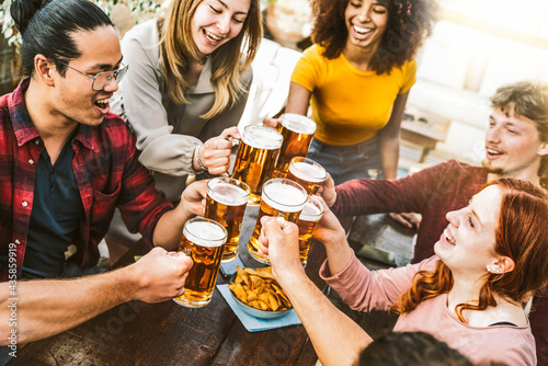 Fototapeta Happy multiracial friends toasting beer glasses at brewery pub - Group of young