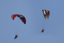 Motorized Hang Gliders In Evening Light Over Countryside  In Spring