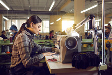 Shoe Or Clothing Factory Worker At Work. Serious Woman Working At Table With Industrial Sewing Machine In Workshop Room, Side View Profile Portrait. Footwear And Clothes Manufacturing Industry Concept
