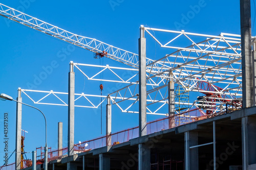 Slika na platnu Closeup of Trade Center building during construction with steel frame shown against blue sky background