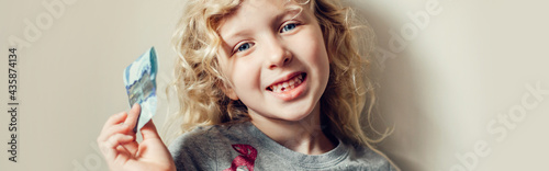 Fotografia Caucasian blonde girl showing her missing tooth in a mouth and holding money from tooth fairy