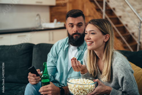 Couple drinking beer and eating popcorn at home while watching television Fotobehang
