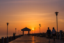 People Take A Leisurely Stroll On A Wooden Plank Road By The Sea At A Romantic Moment When The Sun Is Setting