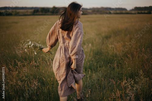 Beautiful woman in linen dress running with wildflowers in hand in summer meadow in sunset Fototapet