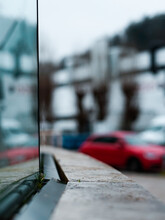Vertical Shot Of A Glass Building Detail With An Unfocused Red Car In The Background
