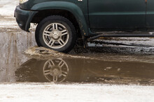 The Wheel Of A Car Driving Through A Deep Muddy Puddle Of Melted Snow. Abnormal Weather Concept. There Is Copy Space. The New Year And Christmas Holiday Is Over. Remains Of Last Year's Snow.