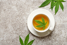 Hemp Herbal Tea And Leaves On Gray Background. Calming Drink Concept