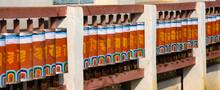 Orange Color Prayer Wheels With Prayer Inscriptions.