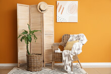 Wooden Folding Screen And Armchair Near Color Wall