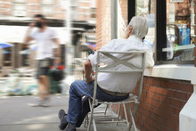 Senior Gray Haired Man Sitting Outside Coffee Shop, Talking On Phone, Enjoying Life. Back View. Prosper, Intelligent, Successful Life, Mature, Slow Living Concept.  New York