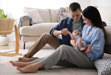 Happy Family With Cute Baby Near Sofa At Home