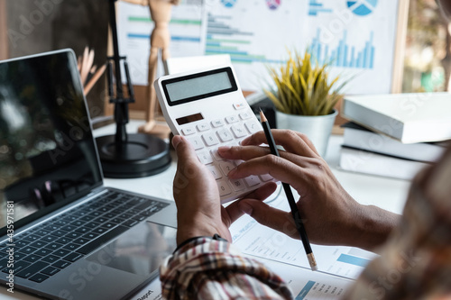 Fényképezés Accountant is using a calculator to calculate company financial figures from earnings papers, a businessman sitting in his office where the company financial chart is placed