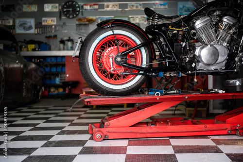 motorcycle raised on the platform to be repaired in a mechanic's shop. mechanics concept. vintage motorcycle