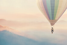 Surreal Woman Enjoying Herself On A Swing Hanging From A Hot Air Balloon