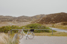White Vintage Ladies Bicycle In The Dunes By The North Sea. Vacation At The Sea By Bike. Bicycle Parking Lot In Nature
