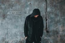 Man Wearing Hood Standing Against Wall