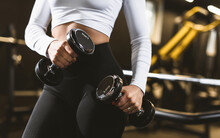Close Up Sport Athletic Fitness Woman Pumping Up Muscles With Dumbbells. Sexy Fitness Girl In Sport Wear With Perfect Body In The Gym Posing Before Training Set. Fitness Woman Model In The Gym.