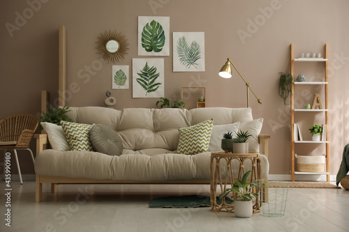 Fototapeta Stylish living room interior with comfortable sofa and beautiful pictures on wal