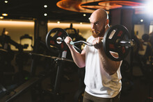 Charismatic Red-bearded Male Bodybuilder Performs Barbell Biceps Exercise In A Sports Club.