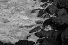 Detail Of White Sea Water Washing Gently Over Black Rocks On The Shore