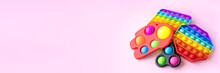 Colorful Anti-stress Fidget Push Pop It Sensory Toys For Children Isolated On Pink Background. Simple Dimple. Top View, Flat Lay. Selective Focus. Banner