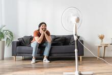 Happy Bearded Man Sitting On Couch Near Blurred Electric Fan
