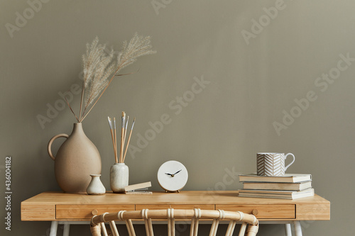 Interior design of neutral bohemian living room interior with stylish desk, armchair, dried flowers in vase, book, decoration, office supplies, copy space, notes and personal accessories. Template.