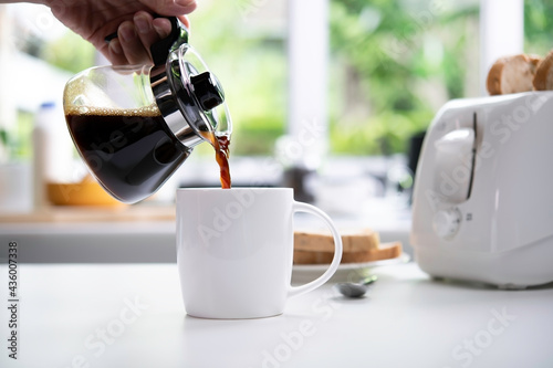 A hand pouring steaming coffee in to a cup on table in the kitchen Fototapet